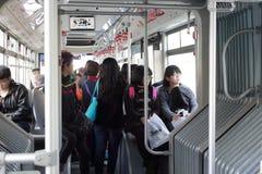 人群在一辆长的公共汽车上明亮 免版税图库摄影
