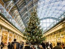 人群在圣诞树,圣Pancras驻地,伦敦,英国附近打旋 免版税库存图片