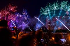 人群无法认出的剪影在城市在晚上观看并且射击烟花 新年假日庆祝,显示 免版税库存照片