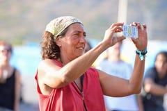 从人群的一名妇女拍与她的智能手机照相机的一张照片在小谎节日 免版税库存照片
