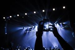 人群的人们在音乐会做录影记录和pics 库存图片