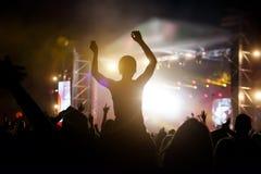 人群的照片,享受摇滚乐音乐会的人们,提高了手和拍手乐趣,活跃夜生活概念 免版税库存图片