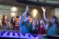 从人群跳舞的DJ的甲板的一个看法在夜总会, 免版税库存照片