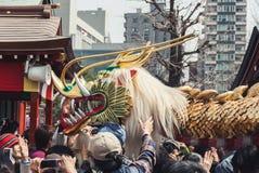 人群围拢龙在金黄龙舞蹈,东京 库存照片