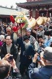 人群围拢龙在金黄龙舞蹈,东京 库存图片