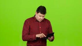 人考虑在计算器的赢利,并且他破产 绿色屏幕 影视素材
