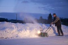 人耕犁雪工作 图库摄影