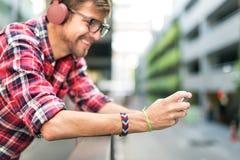 年轻人耳机听的音乐概念 图库摄影
