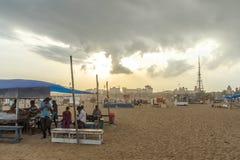 人聚集了在小游艇船坞海滩,购买从商店的eatables有黑暗的天空场面的在日落时间 免版税图库摄影