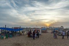 人聚集了在小游艇船坞海滩,购买从商店的eatables有黑暗的天空场面的在日落时间 库存图片
