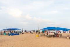 人聚集了在小游艇船坞海滩,购买从商店的eatables 库存图片