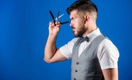 人背心有蝶形领结举行普通刀片蓝色背景 理发师葡萄酒艺术概念 有锐利的理发师有胡子的行家 库存图片