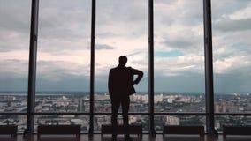 人背面图在全景窗口前面站立有城市视图的正式随员 一个人在大前面站立 图库摄影