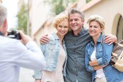 人背面图拍摄男性和女性朋友在城市 免版税图库摄影