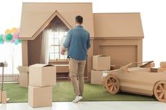 人背面图有搬入新的纸板房子的箱子的 免版税库存照片
