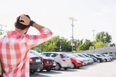 人背面图用在站立在城市街道上的头后的手反对清楚的天空 库存图片