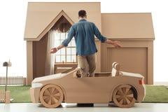 人背面图纸板汽车的在纸板房子前面 图库摄影