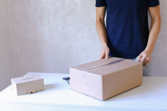 年轻人胶浆磁带箱子和在手上采取小包,站立在P 免版税库存图片