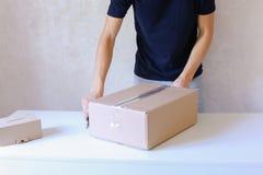 年轻人胶浆磁带箱子和在手上采取小包,站立在P 免版税库存照片