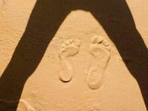 人脚两条轨道在沙子艺术的 库存照片