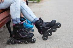 人脚佩带轴向冰鞋 妇女和孩子坐长凳,当rollerblading时 库存照片