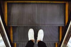 人脚Selfie在白色运动鞋鞋子的在商城顶视图的自动电梯阶梯在葡萄酒样式 免版税库存图片