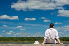 人脱了他的帽子并且坐了看美丽的湖 免版税库存照片