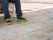 人腿佩带蓝色牛仔裤裤子和区别颜色snea 免版税库存照片