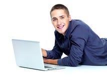 人膝上型计算机微笑的年轻人 图库摄影