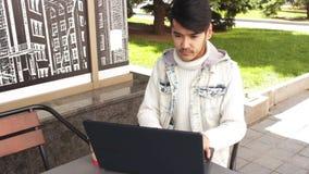 人自由职业者在膝上型计算机的咖啡馆工作 股票录像