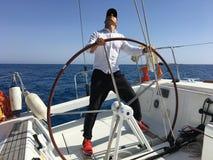 年轻人航行游艇方向盘假期风帆 库存照片