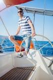 年轻人航行游艇 免版税图库摄影