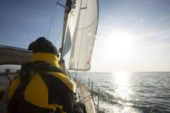 人航行背面图在游艇的在海 免版税库存照片