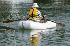 人荡桨充气救生艇小船 免版税图库摄影