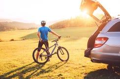 人获得了在山的汽车与他的在屋顶的自行车 登山车概念 图库摄影