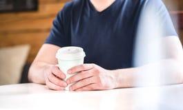 人藏品在手上拿走咖啡杯在咖啡馆的桌上 图库摄影