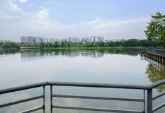 人行桥生锈的扶手栏杆与湖边城市的在背景中 库存照片
