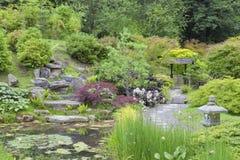 人行道穿过有池塘的,岩石,灯笼东方庭院 免版税图库摄影