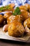 年轻人被烘烤的土豆 库存图片