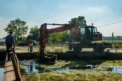 人被管理的挖掘机起重机取消残骸,并且海藻从Naviglio Pavese运河加强在一个晴天 免版税库存照片