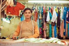 年轻人裁缝在做的礼服一个车间缝合衣裳 免版税库存图片