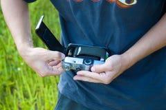 人装载在葡萄酒照片照相机,手的一部影片关闭  免版税库存照片