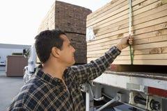 人装货堆在拖车的板条 免版税图库摄影