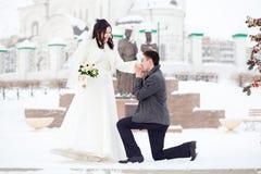 人要求女孩手 冬天婚礼,他的膝盖的新郎在新娘前面一条多雪的街道 婚姻概念 免版税库存照片
