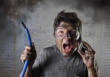 年轻人要求帮助在与肮脏的被烧的面孔的事故以后在滑稽的哀伤的表示 免版税图库摄影