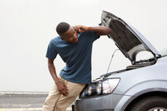 年轻人要求汽车在手机的服务帮助 图库摄影