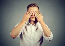 年轻人覆盖物眼睛用两只手 库存照片