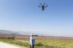 人观看DJI S900寄生虫在飞行中与登上的索尼A7编辑 图库摄影