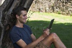 人读书片剂和享受休息在公园在树下 免版税库存图片