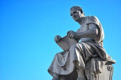 人读书的雕象在有蓝天的意大利 库存图片